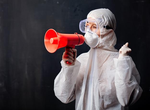 Doktersvrouw die beschermende kleding draagt tegen het virus met megafoon