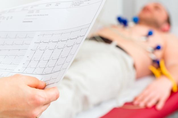 Doktor kontrolliert patiënt ekg in arztpraxis