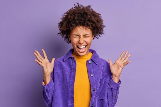 Dolblij afro-amerikaans meisje roept luid uit, houdt de handen omhoog, voelt zich opgewonden en erg blij om geweldig nieuws te horen gekleed in een fluwelen jasje.