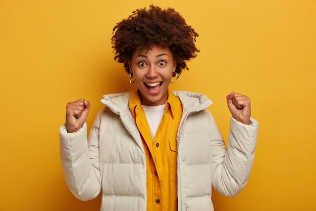 Dolblij afro-amerikaans meisje viert persoonlijke prestaties, voelt zich vrolijk en dolgelukkig, steekt gebalde vuisten op