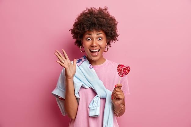 Dolblij afro-amerikaans tienermeisje blij om in vrolijk gezelschap te zijn, steekt hand op, houdt zoete snoep vast, draagt trui vastgebonden over schouder, glimlacht breed,