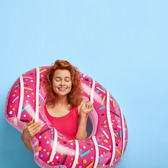 Dolblij blij roodharige vrouw balt tevreden haar vuist, anticipeert op de zomertijd, houdt de ogen gesloten, staat met opgeblazen ring, staat tegen blauwe muur met kopie ruimte. mensen en rust
