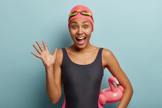 Dolblij blij zwemster steekt handpalm op, roept luid