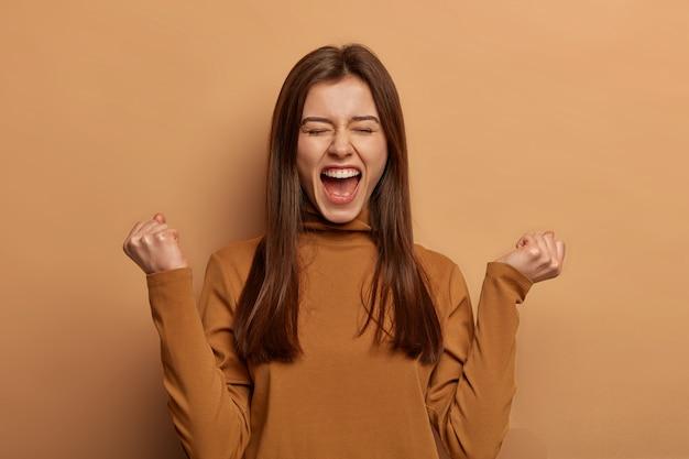 Dolblij brunette vrouw laat vuisten pompen, viert succes, schreeuwt en voelt als kampioen, houdt mond wijd open, draagt coltrui