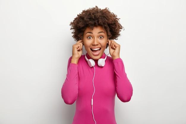 Dolblij gelukkig donkere vrouw met krullend haar, pluggen oren, koptelefoon draagt op nek, gekleed in roze poloneck, geïsoleerd op witte achtergrond, kijkt vrolijk naar camera