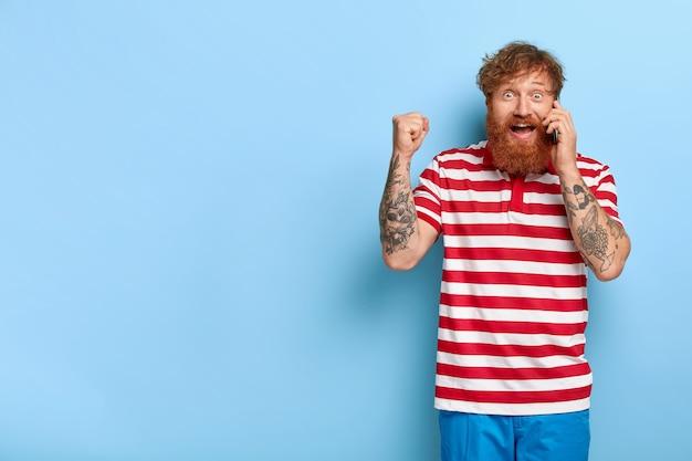 Dolblij gelukkig stijlvolle rode kerel poseren tegen de blauwe muur