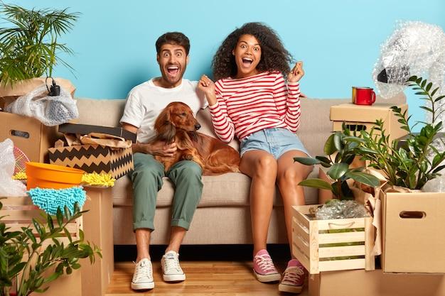 Dolblij getrouwd stel op de bank met hond omgeven door kartonnen dozen