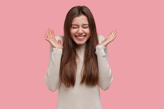 Dolblij glimlachende dame spreidt haar handpalmen, drukt vreugde en geluk uit, vraagt om te stoppen met het vertellen van grappige verhalen, houdt de ogen gesloten