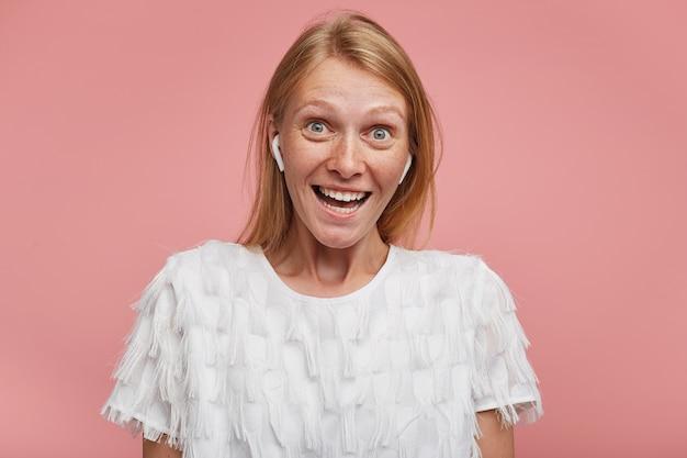 Dolblij jong mooi vrouwtje met foxy haar dat verrast wenkbrauwen opheft terwijl ze naar de camera kijkt met grote ogen en mond open, staande tegen een roze achtergrond
