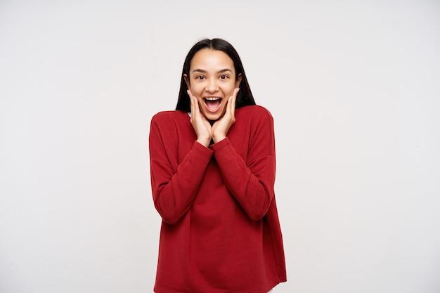 Dolblij jonge aantrekkelijke bruinharige vrouw die haar gezicht met opgeheven handen vasthoudt terwijl ze verbaasd naar de voorkant kijkt, geïsoleerd over een witte muur in een rode sweater