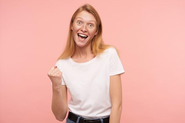 Dolblij jonge aantrekkelijke langharige roodharige vrouw die opgewonden haar vuist opheft terwijl ze met een brede glimlach naar de camera kijkt, staande tegen een roze achtergrond