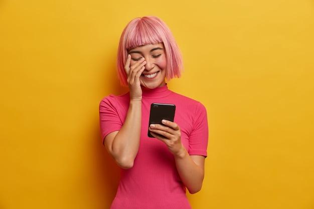 Dolblij jonge aziatische dame heeft bob kapsel, lacht oprecht om bericht in sociaal netwerk, geniet van mobiele communicatie, leest grappig nieuws