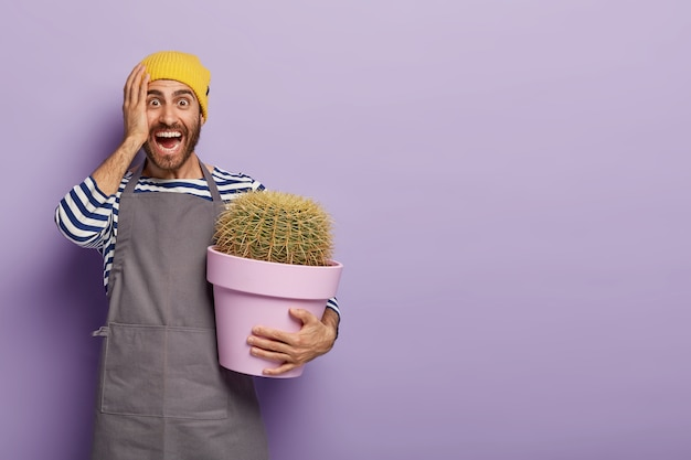 Dolblij jonge blanke man houdt potcactus, gekleed in speciaal werkuniform