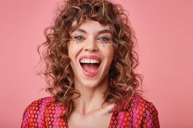 Dolblij jonge blauwogige vrouw met bruin krullend haar die vrolijk kijkt en lacht met wijd open mond, geïsoleerd in een top met gekleurd patroon