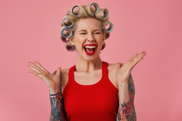 Dolblij jonge blonde vrouw met tatoeages gelukkig schreeuwen met gesloten ogen en emotioneel handen verhogen, met krulspelden op haar hoofd terwijl poseren op roze achtergrond