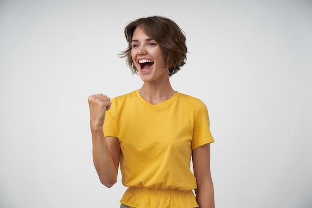 Dolblij jonge brunette vrouw met kort kapsel opzij kijken en lachend met brede mond geopend, vuisten gelukkig opheffen in ja gebaar, geïsoleerd