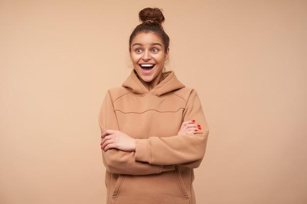 Dolblij jonge knappe brunette vrouw met natuurlijke make-up handen op haar borst kruisen terwijl opgewonden lachen met brede mond geopend, poseren over beige muur