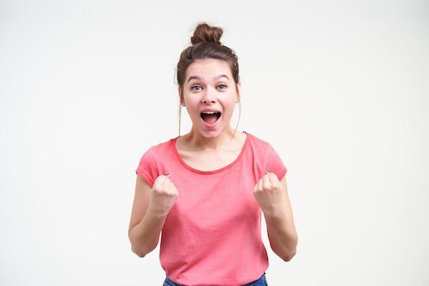 Dolblij jonge mooie brunette vrouw opgewonden schreeuwen met brede mond geopend en emotioneel haar vuisten verhogen terwijl poseren op witte achtergrond