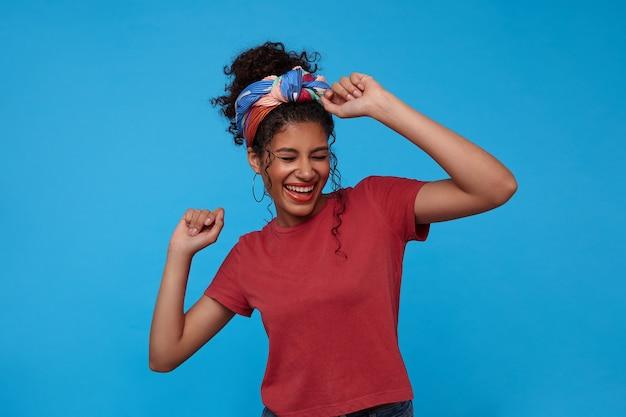 Dolblij jonge mooie krullende vrouw met casual kapsel die haar handen omhoog houdt tijdens het dansen en vrolijk lacht, staande over de blauwe muur