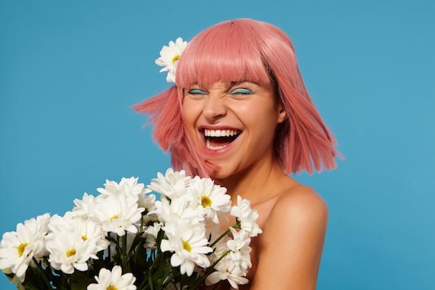 Dolblij jonge mooie roze harige vrouw met gekleurde make-up fronst haar gezicht terwijl ze vrolijk lacht met gesloten ogen, staande met witte chamomiles
