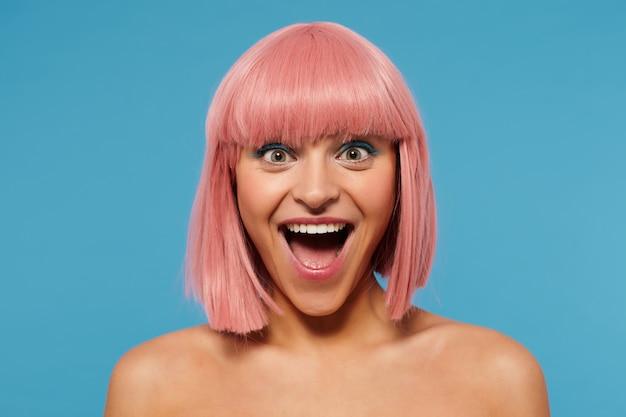 Dolblij jonge mooie vrouw met kort roze kapsel, gekleed in gekleurde make-up op haar gezicht terwijl poseren op blauwe achtergrond, opgewonden kijken naar camera met brede vrolijke glimlach
