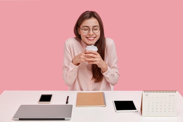 Dolblij jonge student heeft een dromerige uitdrukking, houdt een wegwerpbeker vast met koffie, heeft pauze in de coworking-ruimte, omringd met moderne laptop, tablet