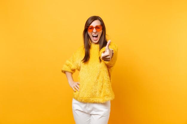 Dolblij jonge vrouw in bont trui, witte broek, hart oranje bril schreeuwen, duim opdagen geïsoleerd op heldere gele achtergrond. mensen oprechte emoties, lifestyle concept. reclame gebied.