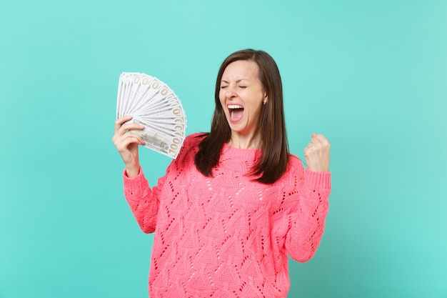 Dolblij jonge vrouw in roze trui schreeuwen, houden veel bos dollars bankbiljetten, contant geld, vuist balde als winnaar geïsoleerd op blauwe achtergrond. mensen levensstijl concept. bespotten kopie ruimte.
