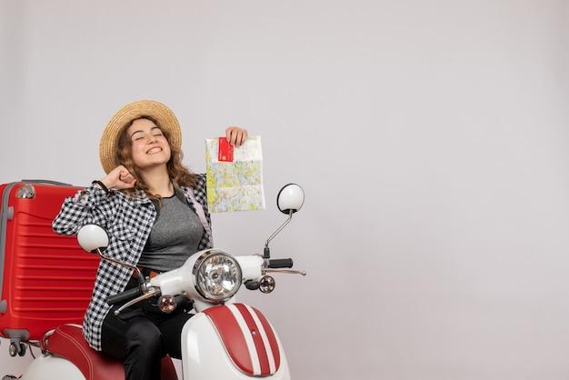 Dolblij jonge vrouw op bromfiets met kaart en kaart op grijs