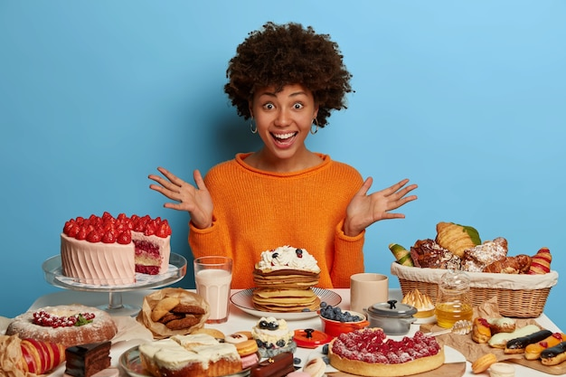 Dolblij jonge vrouw spreidt haar handpalmen, kijkt opgewonden en blij, kan haar ogen niet geloven om zoveel taarten te zien, zit aan een feesttafel, lacht van oprechte emoties