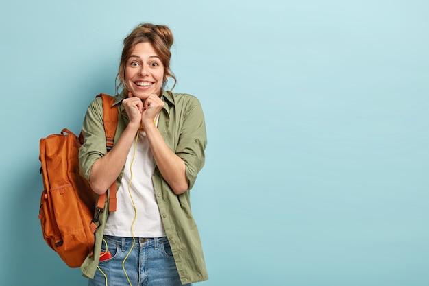 Dolblij jonge vrouwelijke toerist reageert blij als ze iets ongelooflijks ziet, de handen dicht bij de kin gebald houdt