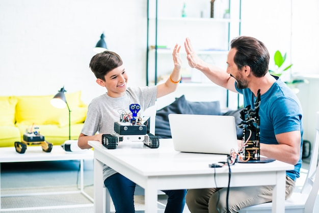 Dolblij jongetje geeft high five aan zijn vader terwijl hij geniet van technische praktijken