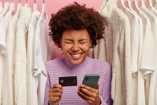 Dolblij krullend vrouwtje gebruikt online bankieren applicatie, maakt elektronisch geld over