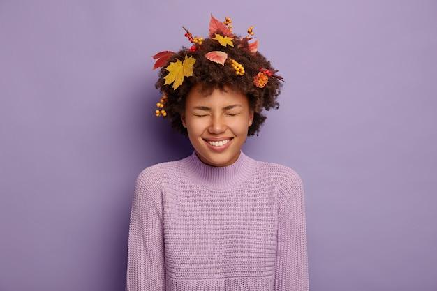 Dolblij, krullende vrouw lacht positief, heeft een herfststemming, lacht breed, maakt grapjes met vrienden, heeft gele esdoornbladeren en lijsterbessen in het haar, gekleed in vrijetijdskleding. geluk, welzijn