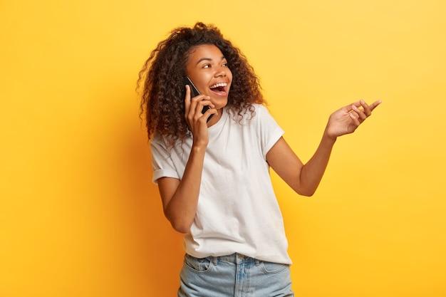 Dolblij lachen gekrulde vrouw geniet van grappig gesprek via mobiele telefoon, handpalm omhoog, gericht op rechterkant, draagt casual outfit