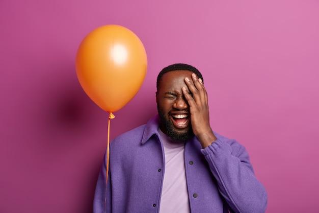 Dolblij man lacht en grappen op feestje, heeft plezier in vrolijk gezelschap van vrienden, houdt de hand op het gezicht, giechelt gelukkig