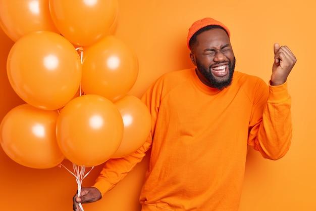 Dolblij mannelijke student viert succes maakt ja gebaar op afstudeerfeest houdt opgeblazen ballonnen gekleed in casual trui geïsoleerd over oranje muur