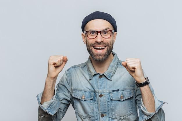 Dolblij mannetje verheugt zich over zijn succes, klemt vuisten op, ziet er vreugdevol uit