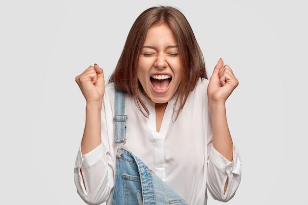 Dolblij meisje balde vuisten van groot geluk, roept luid uit, viert succes op het werk