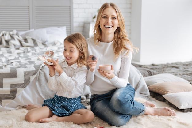 Dolblij meisje houdt een doos met vloeibaar poeder vast en steekt haar vinger erin terwijl haar moeder naar voren glimlacht en een andere poederdoos en een borstel vasthoudt