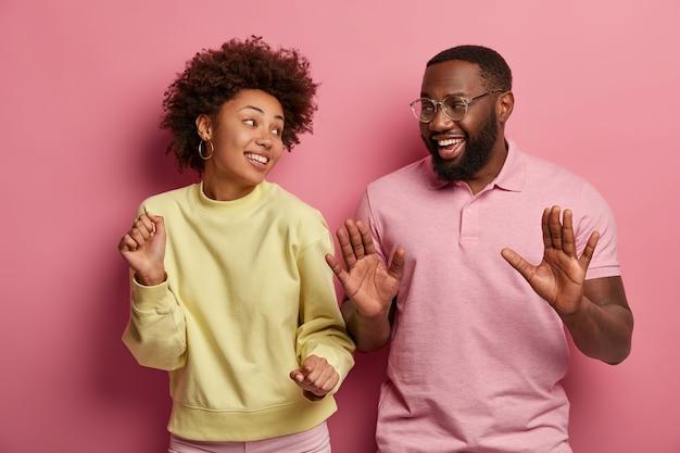 Dolblij millennial vrouw en man, brede glimlach, dans met de handen omhoog, geniet van het ritme van muziek, draag een vrijetijdsoutfit