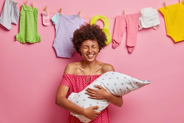 Dolblij moeder met pasgeboren baby op handen geniet van het zoete moment van het moederschap als moeder voor de eerste keer poseert