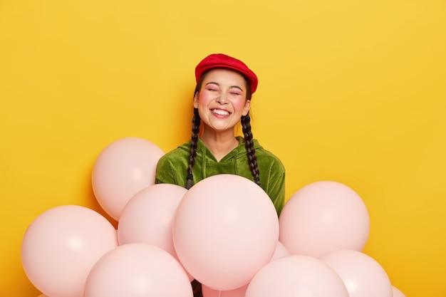 Dolblij, mooie chinese vrouw draagt een rode baret, een corduroy sweatshirt, poseert met luchtballonnen