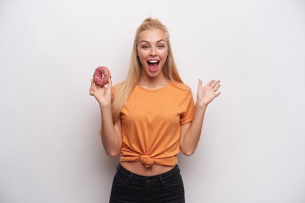 Dolblij mooie jonge langharige blonde vrouw in vrijetijdskleding kijken gelukkig camera met grote ogen en mond geopend, staande tegen witte achtergrond met donut in opgeheven hand