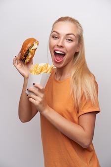 Dolblij mooie jonge langharige blonde vrouw met fastfood in opgeheven handen gelukkig kijken naar camera met grote ogen en mond geopend, geïsoleerd op witte achtergrond