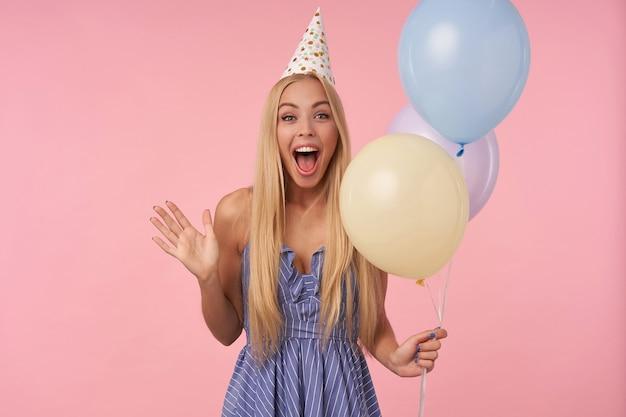 Dolblij mooie jonge langharige vrouw met blond haar poseren in veelkleurige luchtballonnen, gekleed in een blauwe zomerjurk en verjaardagspet, geamuseerd door gasten tijdens het vieren van vakantie
