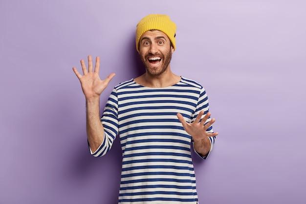 Dolblij ongeschoren duizendjarige man gebaart actief, toont palmen, is in goed humeur, draagt een gele hoed en gestreepte trui