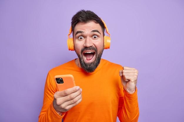 Dolblij ongeschoren man viert uitstekend nieuws balt vuist houdt mobiele telefoon gebruikt draadloze koptelefoon om naar muziek te luisteren geniet van goed geluid draagt oranje trui