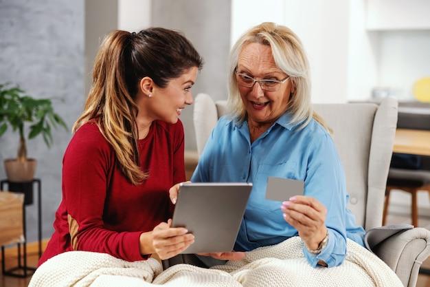 Dolblij, opgewonden moeder en dochter die samen thuis zitten en tablet gebruiken om online te winkelen. de tablet van de dochterholding terwijl de creditcard van de moederholding. moeder zag iets interessants.