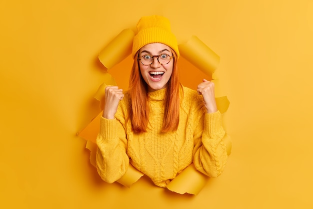 Dolblij roodharige jonge vrouw balde vuisten viert succes roept vrolijk draagt gele hoed en zweet